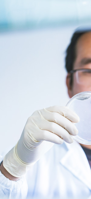 man in lab coat wearing latex gloves holding up petri dish